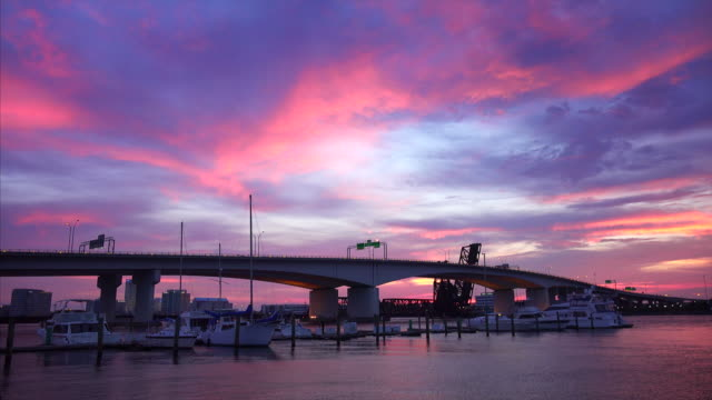 private boats and bridge on st. john's river in jacksonville, florida at sunset - establishing shot点の映像素材/bロール