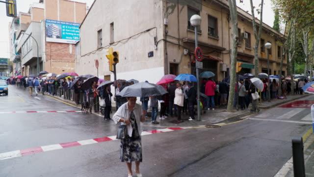 vídeos y material grabado en eventos de stock de private citizens wait in line at a polling station for the independence referendum on october 1 2017 in barcelona spain a an outlawed referendum for... - 2017