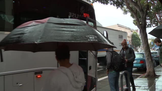 private coaches pull away from curb on rainy downtown streets drive into traffic people wait in line for bus man with umbrella looks at mobile - umbrella stock videos & royalty-free footage
