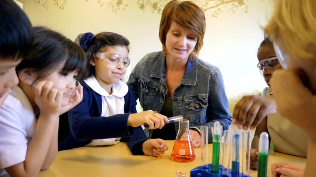 Private elementary school student doing chemistry experiment with teacher and classmates
