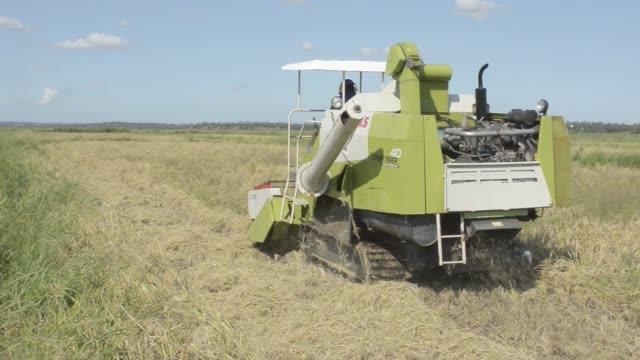 A private farmer uses a small threshing machine to prepare a