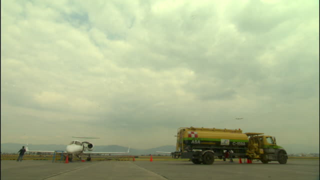 private jet aircraft fuel gasoline tank tanker truck parked on airport tarmac airplane taking off unidentifiable person walking around clouds in sky... - 給油点の映像素材/bロール