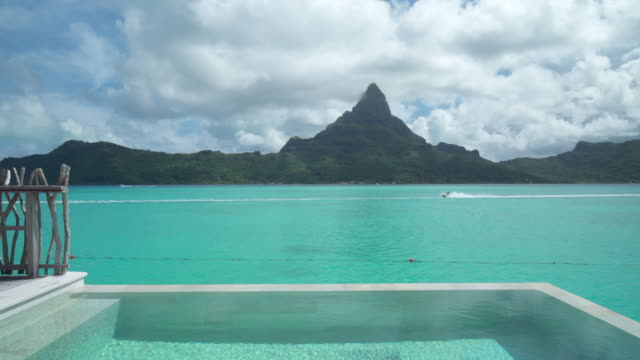 a private pool, lifestyle in a pool on bora bora with mount otemanu at a tropical island resort. - hotelzimmer stock-videos und b-roll-filmmaterial