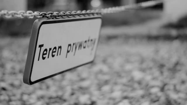 Private property, plate hanging on chain, black and white