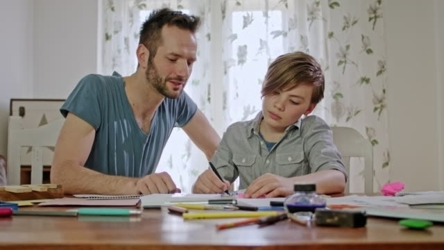 private tutoring lesson for a 10 years old blonde primary school boy while doing his homework by male tutor in his thirties - 10 11 years stock videos & royalty-free footage