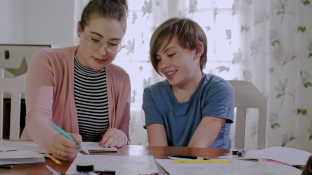 private tutoring lesson for a 10 years old male school child while doing homework together with female tutor in her mid twenties - ausbilder stock-videos und b-roll-filmmaterial