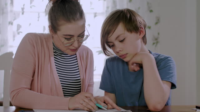 vídeos de stock, filmes e b-roll de private tutoring lesson for a 10 years old male school child while doing homework together with female tutor in her mid twenties - 25 30 anos