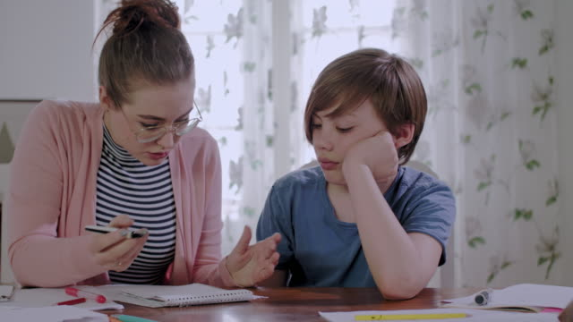 private tutoring lesson for a 10 years old male school child while doing homework together with female tutor in her mid twenties - 10 11 years stock videos & royalty-free footage