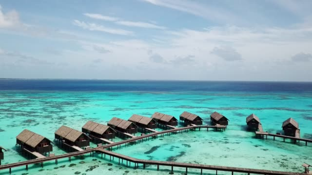 private villas on water in a luxory resort on the maldives - tourist resort stock videos & royalty-free footage