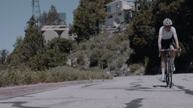 pro cyclist in hard physical training, breathing hard as he climbing winding mountain road - uphill stock videos & royalty-free footage