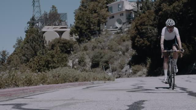 vidéos et rushes de pro cyclist in hard physical training, breathing hard as he climbing winding mountain road - qui monte