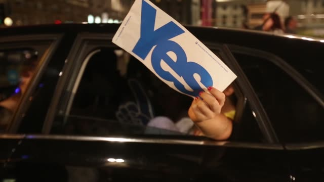 Pro independence yes campaign supporters hold Royal Standard of Scotland flags during a demonstration at George Square on the night of the Scottish...