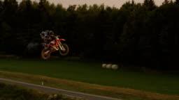 AERIAL SLOW MOTION: Pro motocross biker performing superman trick over sunset sun