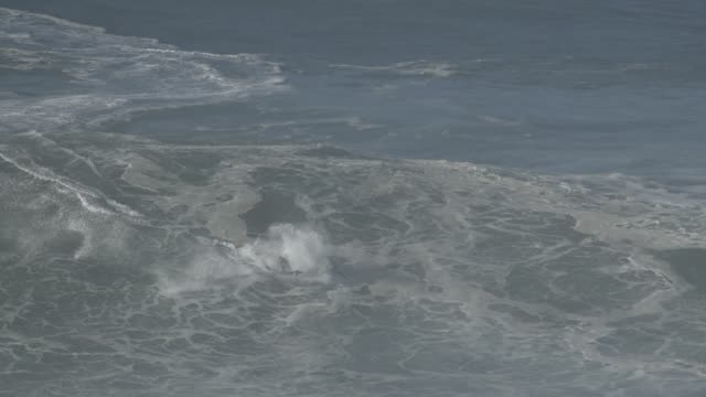 Pro surfers on the massive XXL waves off the Praia do Norte at Nazare Portugal