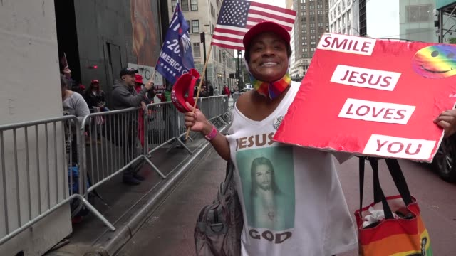 vídeos de stock, filmes e b-roll de pro trump supporters unfurl giant 'trump law and order' flag in front of trump tower, march down 5th ave passed st patrick's cathedral to nypd police... - distrito dos teatros
