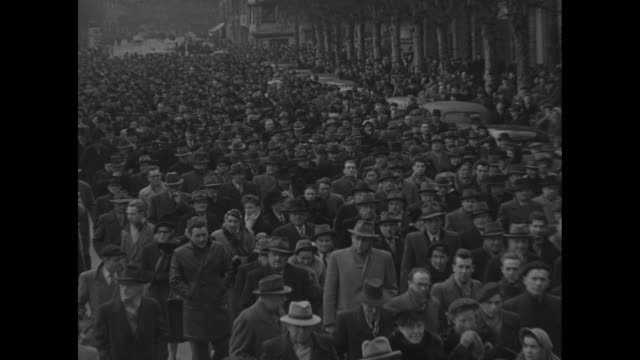 probably in oradour-sur-glane: large somber procession of mourners march down street in memoriam of the oradour-sur-glane world war ii massacre... - steeple stock videos & royalty-free footage