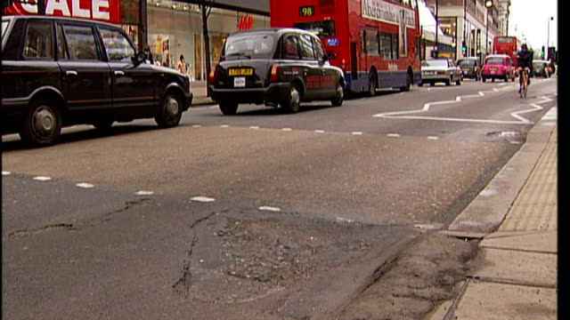 problem of potholes in london t23030703 / tx cyclist riding over uneven road surface end lib - uneven stock videos & royalty-free footage