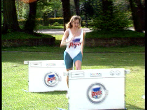 """problem; """"persil power"""" problem; england: london: battersea park seq sally gunnell jumping over persil hurdles - battersea park stock videos & royalty-free footage"""
