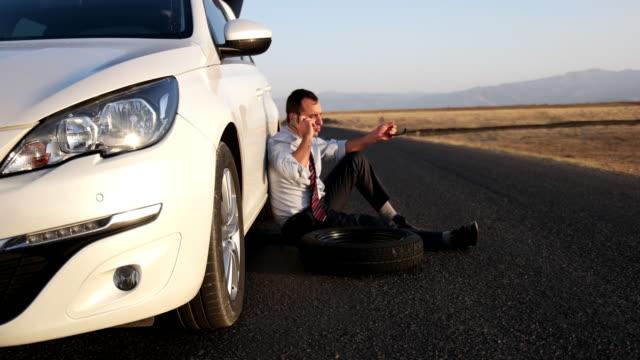 stockvideo's en b-roll-footage met probleem met een auto. een kapotte auto op de weg - piercen