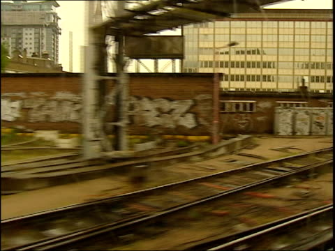 vídeos de stock, filmes e b-roll de problem with graffiti in london itv london forward past graffiti covered wall graffiti on metal shutters on side of train - itv london tonight