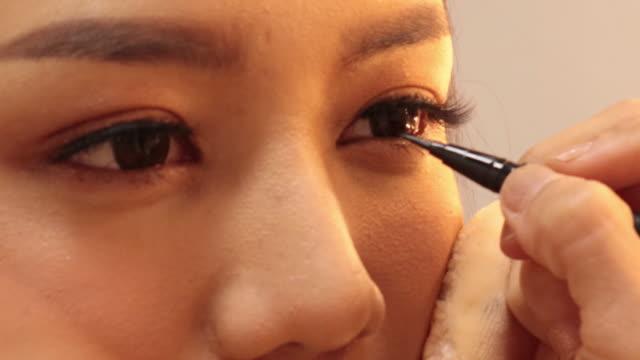 vidéos et rushes de processus de maquillage professionnel pour la belle et magnifique femme dessiner des flèches sur l'œil, eye-liner assis au studio. - appliquer