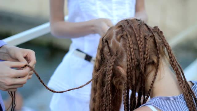 vídeos de stock e filmes b-roll de processo da trança em vermelho unbraid de pêlo menina adolescente - trançado