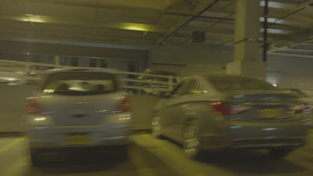 vídeos de stock, filmes e b-roll de process plate 3/4 back left of car driving in parking garage. parked cars visible. - stationary process plate