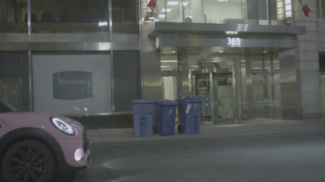 Process Plate 3/4 BACK LEFT OF CAR DRIVING ON CITY STREET IN TORONTO. OFFICE BUILDINGS, PEDESTRIANS, BUSINESSES, AND VISIBLE. FRONT OF PINK MINI COOPER VISIBLE.