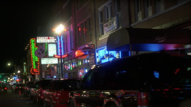 process plate 3/4 back right of downtown nashville. cars parked on curb outside bars, restaurants, and shops. neon signs and lights. urban area. pedestrians visible.