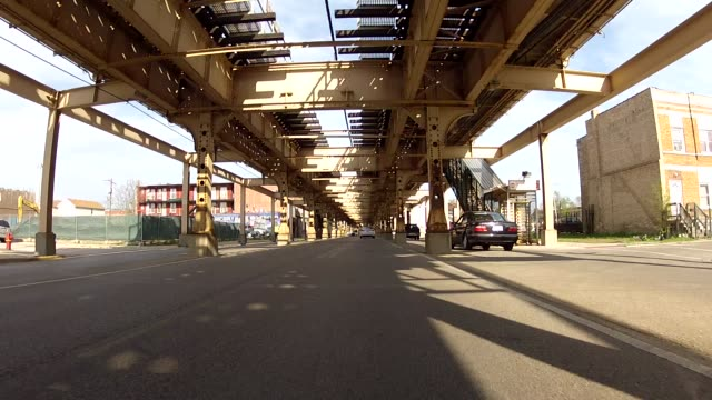 process plate driving straight forward pov on city street with other cars under elevated tracks. could be part of car chase. - driving plate stock videos & royalty-free footage