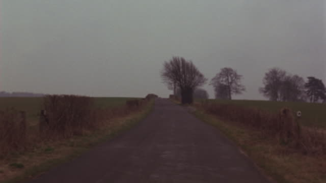 process plate straight back of english countryside. bare trees, fields, farmlands, wire fence seen. - parking stock videos & royalty-free footage