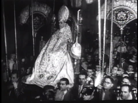 EVE 'HOLY YEAR' CEREMONY Procession carrying Papal Tiara down hallway Pope Pius XII being carried in sedia gestatoria down hallway followed by...