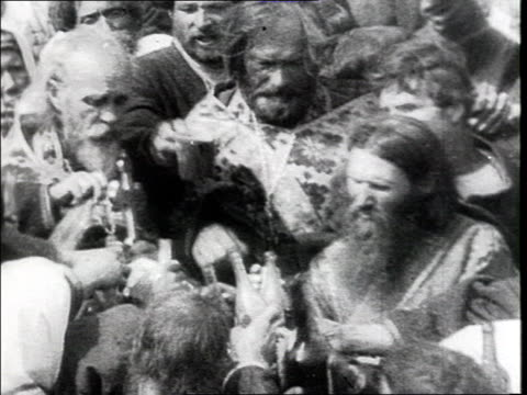 procession in a russian village : procession w/ religious banners, people passing past camera, priests blessing people, surrounded by the crowd,... - anno 1925 video stock e b–roll
