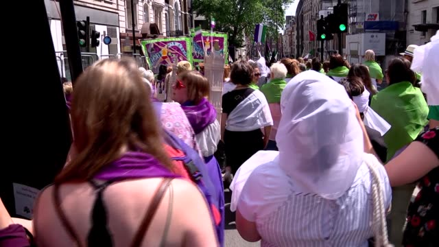 procession in london to mark 100th anniversary of womens' suffrage; england: london: ext marchers along street wearing the green, white and violet... - 一百週年紀念 個影片檔及 b 捲影像