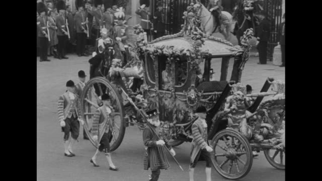 procession leaves buckingham palace and curves around queen victoria memorial / the queen is seen inside the gold state coach / spectators wave... - coronation of queen elizabeth ii stock videos and b-roll footage