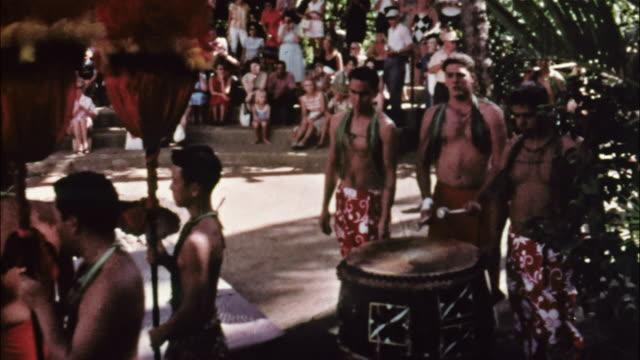 vídeos y material grabado en eventos de stock de a procession of hawaiians brings food for a  luau; women dance a graceful hula; a tahitian woman performs a dance. - isleño del océano pacífico