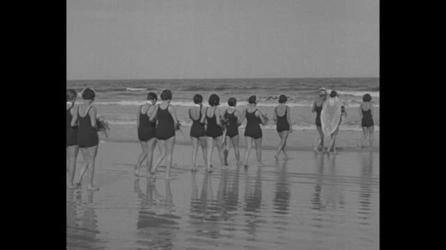 procession of lifeguards wearing hats and carrying bouquets along beach fern arrangement in container on sand bride and groom as neptune carrying... - neckwear stock videos and b-roll footage