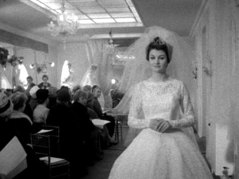 stockvideo's en b-roll-footage met a procession of models wearing wedding dresses walk past the camera at a fashion show 1961 - kleding