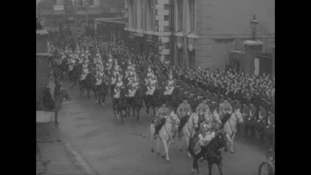 a procession of numerous and varied mounted british military ride next to st james palace with royal carriage / grenadier guards with large crowd... - british military stock videos and b-roll footage