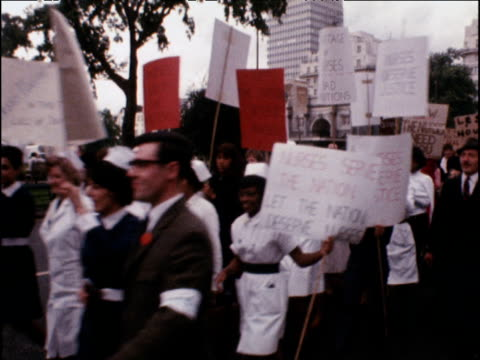 procession of nurses in uniform walk past camera holding placards in protest to pay and working conditions 15 aug 68 - gehaltsstreifen stock-videos und b-roll-filmmaterial