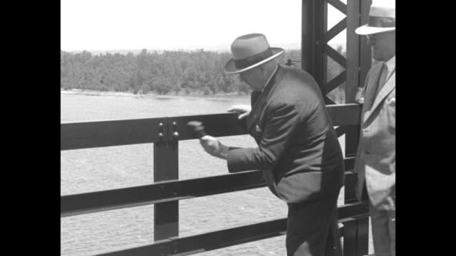 procession of people crossing champ clark bridge walking past camera / illinois governor len small on illinois side of bridge preparing to hammer... - mississippi flod bildbanksvideor och videomaterial från bakom kulisserna