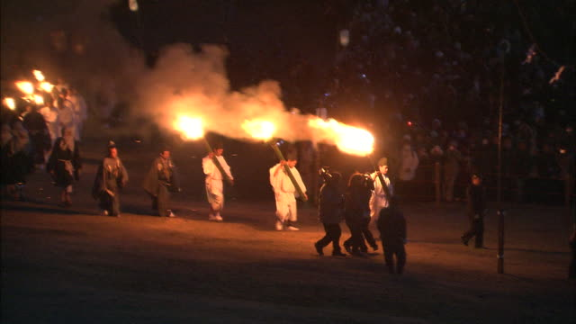 a procession of shinto priests carry torches around a brazier. - shinto stock videos and b-roll footage