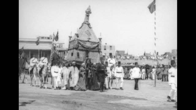 procession of soldiers wearing fezzes on horseback flags on tall poles line sides / horsedrawn carriage with king fuad passing / fuad with high... - passing a note stock videos and b-roll footage