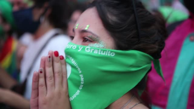 stockvideo's en b-roll-footage met pro-choice demonstrators follow the deputies sessions on a giant screen placed outside the national congress during a vigil as deputies vote to give... - argentinië