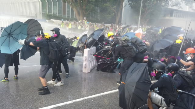 prodemocracy protesters stand against the spray from a water cannon during clashes with police outside the central government offices on september 15... - menschenreihe stock-videos und b-roll-filmmaterial