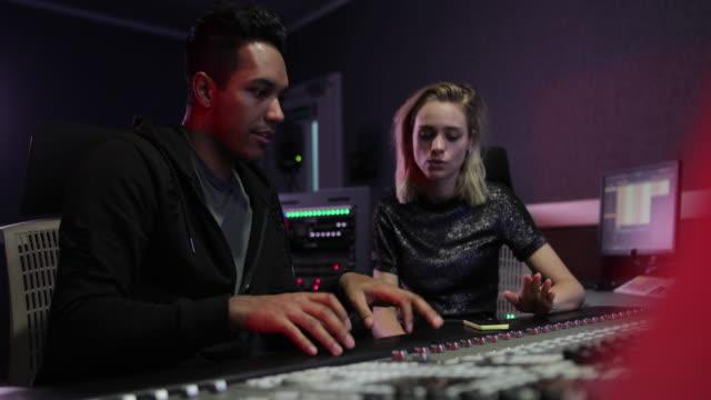 producer and singer playing back a recorded track - låtskrivare bildbanksvideor och videomaterial från bakom kulisserna