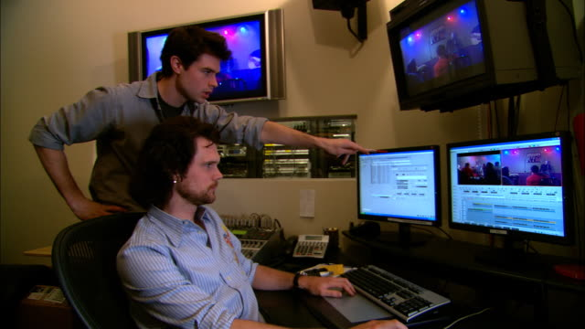 MS Producer standing beside editor in studio and pointing at computer monitor/ New York, New York