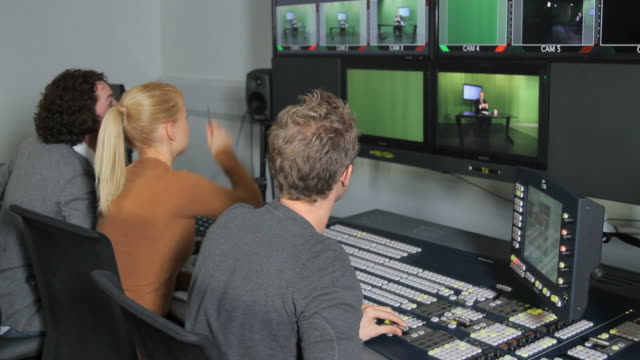 Producers working in television studio control room