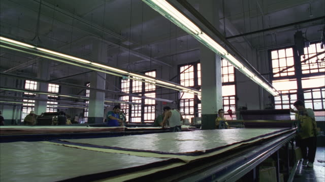 vidéos et rushes de ws production line in garment factory, workers rolling out fabric - usine textile