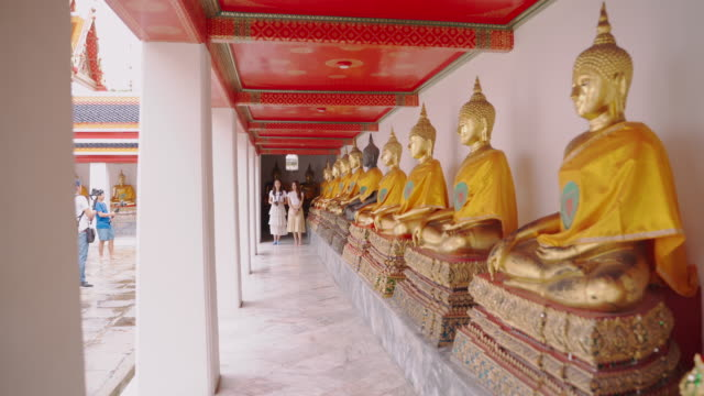 """produktionsteam filmt für reisewerbung.making video-blog guide to tourist attractions to publish a tour on her channel at """" what pho """" landmark of bangkok in thailand - buddha stock-videos und b-roll-filmmaterial"""